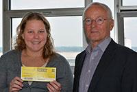 Jürgen Heinrich von der Westfälisch Lippische Universitätsgesellschaft (WLUg) übergibt Studentin Marina Ragusin aus Brasilien ein Ticket für das Campus Festival. Foto: Universität Bielefeld