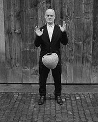 """Das Plakatmotiv für die BGHS-Jahrestagung zeigt den Schweizer Kunstsammler Uli Sigg, wie er eine Coca Cola-Urne des Künstlers Ai Weiweis fallenlässt. Das Motiv ist Teil der Fotoserie """"Fragments of History"""" von Manuel Salvisberg. Mit dem Motiv greifen die Veranstalter das Seminarthema auf: Wie ist das Verhältnis zwischen Momentaufnahme und Handlungsabfolge, wenn nur ein Moment dargestellt wird? Foto: Manuel Salvisberg"""