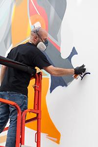 Der Künstler SatOne ist aus München nach Bielefeld gereist, um, gemeinsam mit dem Graffiti-Künstler Roid, die Trennwand zu besprayen. Foto: Universität Bielefeld