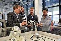 Robotik ist ein Thema beim gemeinsamen Studiengang BioMechatronik: Die Professoren Axel Schneider (Fachhochschule, l.) Ulrich Rückert (Universität, 3. v. l.) sowie die neuen Studierenden Niels Weiler und Moaid Othmann (rechts). Foto: Universität Bielefeld