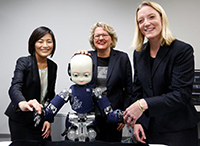 Prof. Yukie Nagai PhD von der Universität Osaka (l.) präsentiert Wissenschaftsministerin Svenja Schulze (Mitte) und Prof. Dr. Friederike Eyssel den kindgroßen Roboter iCub im Emergent Robotics Lab. Foto: Ina Fassbender