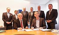 Erster Direktor Thoma Keck (l.) und Prof. Dr. Oliver Razum unterzeichnen die Verträge, hinter ihnen stehen die Vertreter der anderen Stifter (v.l.): Frank Böker (Johanniter Ordenshäuser), Prof. Dr. Lothar Feige und Peter F. Schauerte (AHG Klinikgruppe), Achim Schäfer (MZG Bad Lippspringe), Andreas Finkel (MEDIAN Kliniken), Günther Knauer (VdPK-NRW). Nicht im Bild Dr. Ursula Becker (Dr. Becker-Kliniken). Foto: Deutsche Rentenversicherung Westfalen