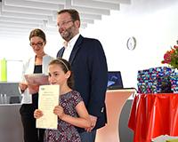 """Stolz präsentiert Romaisae Nssis ihre Abschlussurkunde von """"Welcome Science""""."""