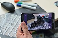 Mit speziellen Apps – hier von der Bielefelder Firma Raumtänzer – lassen sich aus Print-medien Extra-Informationen als erweiterte Realität auf dem Smartphone darstellen. So wirkt es, als würde das Motorrad auf dem Schreibtisch stehen. Foto: CITEC/Universität Bielefeld