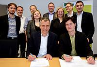 Die Vertreter von Kiron Open Higher Education sowie die Vertreter der Universität Bielefeld sind zur feierlichen Vertragsunterzeichnung in der Universität Bielefeld zusammengekommen. Foto: Universität Bielefeld