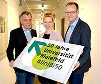 Rektor Gerhard Sagerer, Dr. Sarina Bornkessel und Martin Knabenreich (v.l.) mit dem neuen Jubiläumslogo. Foto: Universität Bielefeld