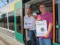 Carsten Lange, moBiel, und Dr. Guido Elsner (v.l.) bereiten die Matherätselaktion in den Bielefelder Stadtbahnen vor. Am Montag, 5. August, geht's los. Foto: Universität Biele-feld