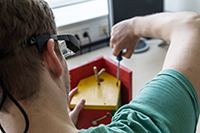 The precursor model to the Avikom glasses can, for example, help sheltered workshop workers assemble wooden bird houses. Photo: CITEC/Bielefeld University