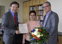 Universitätskanzler Hans-Jürgen Simm (links) und Bibliotheksdirektor Michael Höppner gratulieren der Jubilarin Henrike Thies