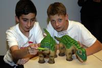 Emrecan und Philip, 7. Klasse Helmholtz-Gymnasium, experimentieren mit Saurier-Robotern.