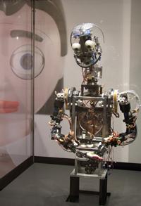 Roboter wie Barthoc und Flobi (als Projektion im Hintergrund), die an der Universität Bielefeld entwickelt wurden, könnten zukünftig Helfer im Alltag werden, zum Beispiel indem sie ältere Menschen im eigenen Haushalt unterstützen.