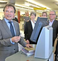 Kanzler Hans-Jürgen Simm (links) nutzt den neuen Ausleihterminal als einer der Ersten.