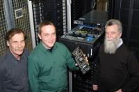 Die Physiker Professor Dr. Edwin Laermann, Dr. Olaf Kaczmarek und Professor Dr. Frithjof Karsch (von links): Kaczmarek zeigt eine Grafikkarte des neuen Hochleistungsrechners der Theoretischen Physik. Der neue Rechner wird mit 400 modernen Grafikkarten ausgestattet.
