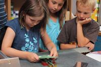Kinder erproben die neue Schuldruckerei der Lernwerkstatt der Universität Bielefeld.