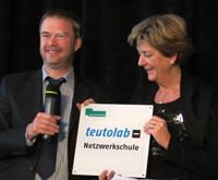 Prof. Dr. Jochen Steil übergibt Schulleiterin Rita Klötzer das teutolab-Netzwerkschulen-Logo der Universität Bielefeld.