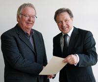 Der Kanzler der Universität Bielefeld Hans-Jürgen Simm (rechts) überreicht Rolf Strachau die Urkunde anlässlich seines Dienstjubiläums. Foto: Universität Bielefeld
