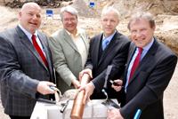 Heinrich Micus, Prof. Dr. Andreas Hütten, Dr. Martin Chaumet und Hans-Jürgen Simm (v.l.) versenken die Kapsel mit der Urkunde im Grundstein.