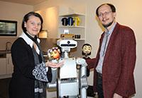 Prof. Dr.-Ing. Britta Wrede und Prof. Dr. Helge Ritter begrüßen den Roboter der Firma Meka Robotics. Der neue Service-Roboter soll mit einer Variante des Flobi-Kopfes (Hintergrund) ausgestattet werden. Foto: Universität Bielefeld