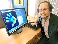 """Forscherinnen und Forscher befassen sich in dem Projekt auch mit Sensortechnik. Prof. Dr. Helge Ritter demonstriert """"Myrmex"""". Der Forschungsprototyp erkennt den unterschiedlichen Druck, den Objekte ausüben, die darauf platziert werden. Foto: Universität Bielefeld"""