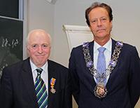 Er erfuhr erst vor Ort von der königlichen Ehrung: Professor Dr. Friedrich Götze (links) von der Universität Bielefeld ist neues Mitglied im niederländischen Orden von Oranien-Nassau. Rob van Gijzel (rechts), Bürgermeister von Eindhoven, verlieh dem Mathematiker den Ordner.