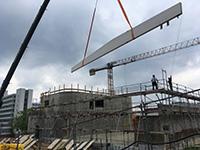 Juni 2020: Der erste von insg. zwölf meterlangen und tonnenschweren Stützbalken aus Brettschichtholz schwebt über dem Rohbau des Hörsaalgebäudes an der Konsequenz. Beim Einsatz der Balken als Deckenkonstruktion für den zukünftigen Hörsaal ist Präzisionsarbeit gefragt.