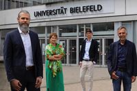 Prof. Dr. med. Björn Spittau (vorne links) ist als erster neuer Professor an die Medizinische Fakultät OWL berufen worden. Ihm gratulieren (v. li.)  Prof'in Dr. Claudia Hornberg, Dekanin der Medizinischen Fakultät OWL, Fakultätsgeschäftsführer Dr. Frank Lohkamp und Prof. Dr.-Ing. Gerhard Sagerer, Rektor der Universität Bielefeld. Foto: Universität Bielefeld/S. Sättele